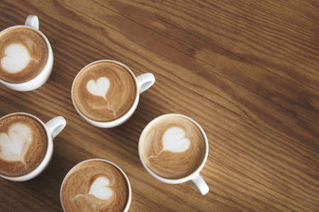 automat: Six lovely white ceramic cups with cappuccino isolated on wooden table. Foam on top in flying heart shape