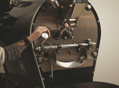Brutal tattooed barista hand is ready to pull lever to open door in the best coffee roasting professional machine