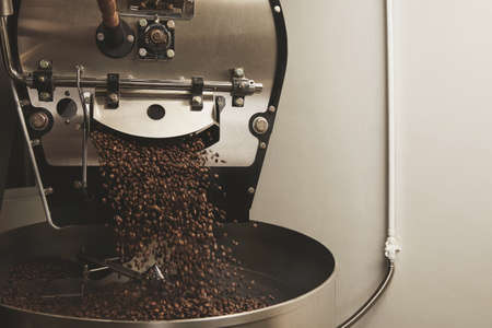 Roaster: Hot freshly baked coffee beans fall from best professional large coffee roaster being poured into the cooling cylinder with motion blur on the beans Side centered