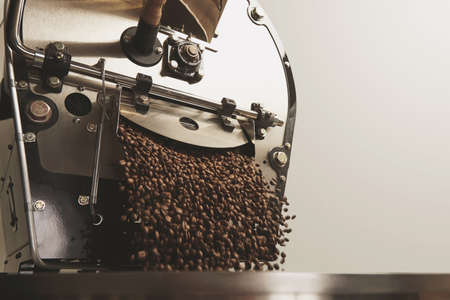 Roaster: Many hot freshly baked coffee beans fall from best professional large coffee roaster being poured into the cooling cylinder with motion blur on the beans Side centered
