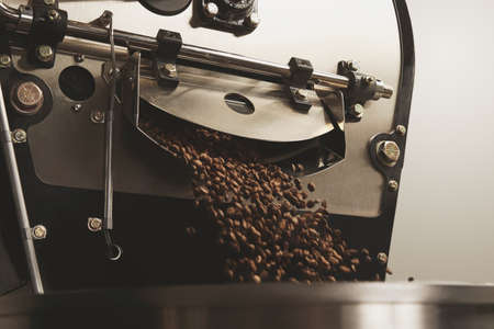 Roaster: Hot freshly baked coffee beans fall from best professional large coffee roaster being poured into the cooling cylinder with motion blur on the beans Close up