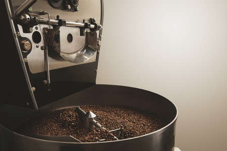roasting: Freshly baked aromatic and dark coffee beans in the best professional roasting machineIndustrial concept LANG_EVOIMAGES