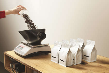 origin of man: Woman hand pours freshly baked aromatic coffee beans to weight before packing in bulk bag package. Professional roastery business. Everything on working wooden table
