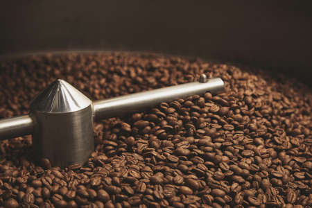 origin of man: Dark, aromatic, chocolate coffee beans freshly baked and hot cool dawn inside the best professional roasting machine close up focus LANG_EVOIMAGES