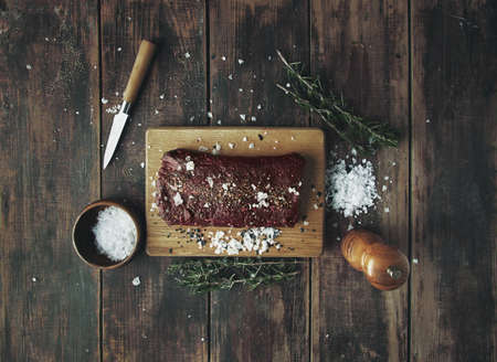 peppered: Salted peppered piece of meat ready to grill on wooden table between herbs and spices on wooden vintage table top view