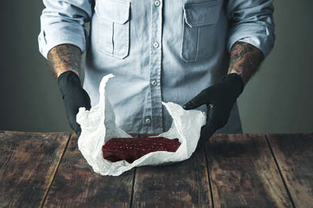 tattoed: Unrecognizable tattoed butcher in black gloves uncovers piece of luxury whale meat from white craft paper on rustic wooden table