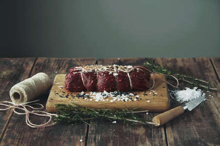 peppered: Rope tied salted peppered piece of meat ready to smoke on wooden table between herbs and spices on wooden vintage table