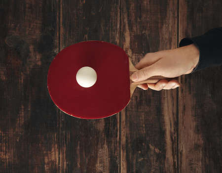 ping pong: Hand holds one professional rocket above wooden aged table with ball on it and ready to play ping pong LANG_EVOIMAGES
