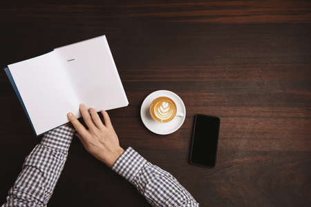 table of contents: Top view accountant hands in plaid shirt  hold opened note book with contents near cup with cappuccino on white ceramic tea plate and phablet phone on red wooden table during coffee break