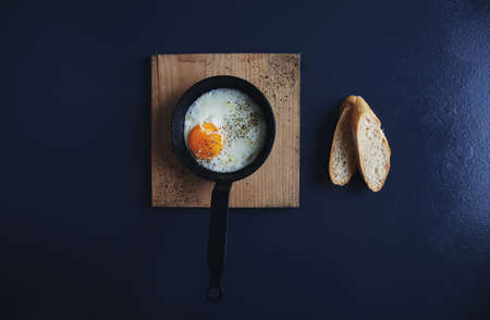 baguet: Top view tasty healthy breakfast: fried egg in small vintage pan on wooden pad and two slices of french crunchy bread isolated on vintage rustic table LANG_EVOIMAGES