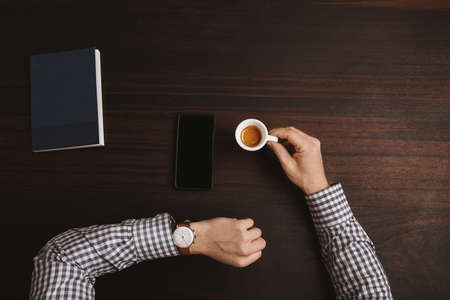 luxury watches: Businessman hands in plaid shirt watching time on his luxury watches with leather strap hold ceramic cup with espresso on red wooden table in cafe shop during his coffee break. Smartphone and note book near