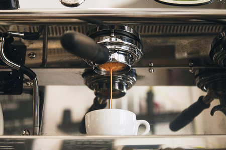 Fresh espresso coffee brewing through the bottomless portafilter in white ceramic cup in artisan cafe shop. Vintage professional coffee machine, front view in center, mirrored background Standard-Bild
