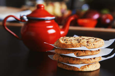 vintage: Morning set. Tasty crunchy homemade cookies on black table in front of unfocused red vintage teapot vith hot beverage and vegetables and other things
