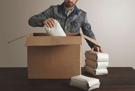 hermetic: Bearded brutal man in jeans work jacket puts blank sealed hermetic packages inside big carton paper box on wooden table. Special delivery, retail shipping post box