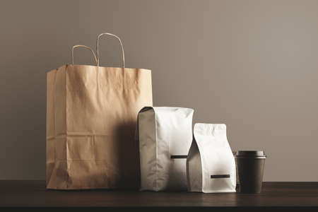 bagged: Presentation of retailer package set: craft paper bag, big pouch, small container and take away glass with cap. Filled with goods, blank labeled, merchandisepack LANG_EVOIMAGES
