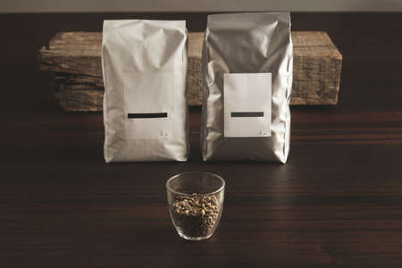 tare: Distribution pack: Two big hermetic pouches white and silver metallic, with blank labels presented in front of rustic wooden brick, behid a transparent glass with raw sampled coffee beans on red table, isolated LANG_EVOIMAGES