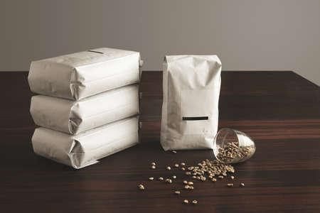 Big hermetic package with blank label presented near other four lying pouches filled with roasted coffee, near fallen transparent glass with raw sampled coffee beans spreaded on red table