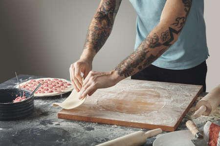 to flatten: Tattooed chief man cooks pelmeni or dumplings or ravioli in special mold. Flip flatten dough in air above wooden board on rustic table