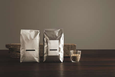 hermetic: Retail pack: Two big hermetic pouches white and silver metallic, with blank labels presented in front of rustic wooden brick, near transparent glass with raw sampled coffee beans on red table, isolated