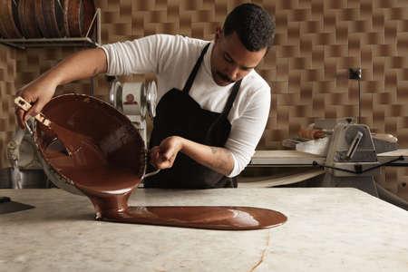 Zwarte man professionele chief schenkt lekkere gesmolten chocolade van de ene grote stalen pot vintage marmeren tafel in zijn artisanale rustieke keuken met retro machines industrie. Weerspiegeld in chocolade op tafel.