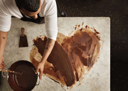 Top view professional black baker uses hot chocolate to draw a lovely heart, before makint sweet organic bars as romantic gifts for valentine day. Isolated on marble table in artisan retro laboratory