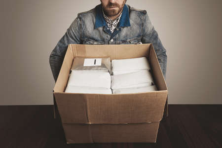bagged: Bearded man loader at work takes big opened carton box with white packages inside filled with coffee or tea, one different silver package with blank label in corner. Isolated on white, red wooden table