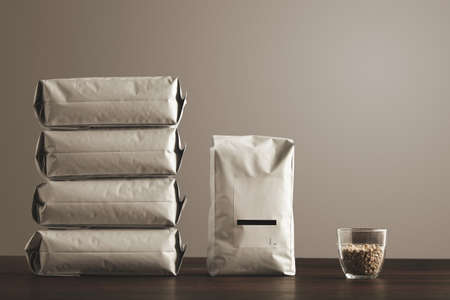hermetic: Retail pack: Big hermetic package with blank label presented near other four lying pouches filled with goods, near transparent glass with raw sampled coffee beans on red table, isolated