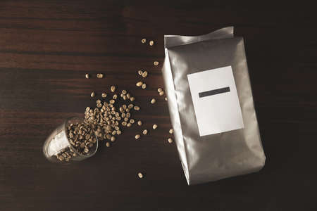 hermetic: Top view on big hermetic silver metallic package filled with freshly baked roasted coffee to preserve its aroma on red wooden table near fallen transparent cup with spreaded raw green peeled coffee beans