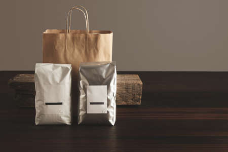 polythene: Retailer merchandise pack: Two big hermetic pouches white and silver metallic, with blank labels presented in front of craft paper bag and rustic wooden brick on red table, isolated. Coffee or tea distribution