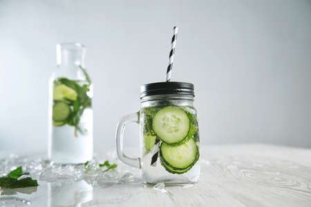 cool down: Cucumber mojito lemonade without alcohol. Fresh summer drink to cool down with mint, mineral water and ice. Rustic jar in front and bottle with beverage behind