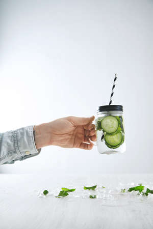 cool down: Bartender hand holds fresh cold lemonade from cucumber and mint in rustic jar with striped straw above table with melted ice. Offering drink to cool down in summer heat