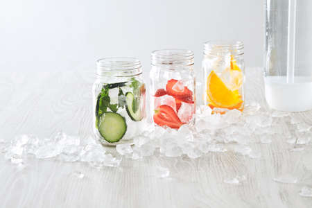 cool down: Closeup rustic jars with ice and various fillings: orange,strawberry,cucumber and mint prepared to make fresh homemade lemonade with sparkling water from syphone Healthy beverage to cool down in summer
