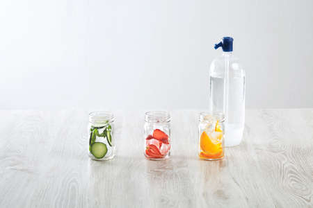 cool down: Rustic jars with ice and various fillings: orange,strawberry,cucumber and mint prepared to make fresh homemade lemonade with sparkling water from syphone Healthy beverage to cool down in summer time