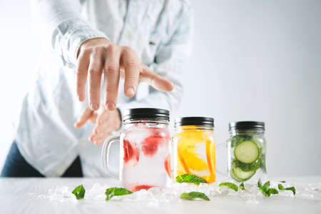 first move: Hand takes one of rustic jars with cold fresh homemade lemonades from strawberry, orange, cucumber, ice and mint Close focus on first jar, action move, summer mood LANG_EVOIMAGES