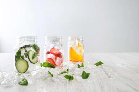 cool down: Closeup rustic jars in crashed ice cubes with orange,strawberry,cucumber and mint prepared to make fresh homemade lemonade with sparkling water Healthy beverage to cool down in summer