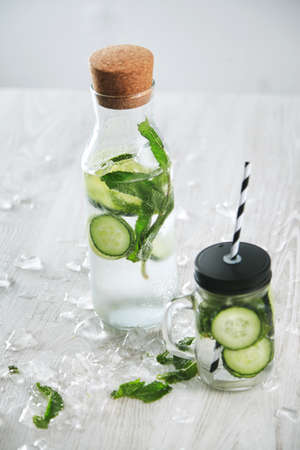 cool down: Cucumber mint drink Fresh summer homemade lemonade to cool down with mineral water and ice. Rustic jar with straw and closed vintage bottle with beverage, top view