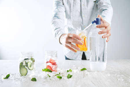 cool down: Bartender makes homemade lemonade, pours sparklig water from syphone to rustic jar with orange slices Jars with cucumber, mint, strawberry and ice cubes stay ahead Cool down healthy summer beverage