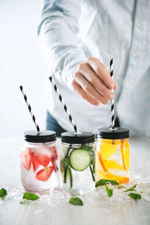cool down: Bartender puts striped drinking straws in jars with fresh cold homemade lemonades made from ice, strawberry, orange, cucumber and mint. Crashed melted ice around Cool down beverages for summer time LANG_EVOIMAGES