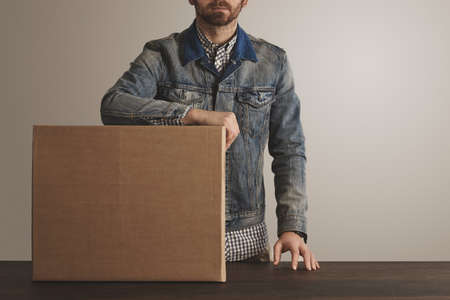 stays: Bearded brutal courier in jeans work jacket stays near presented big carton paper box with goods on wooden table. Special delivery, retail shipping post box LANG_EVOIMAGES