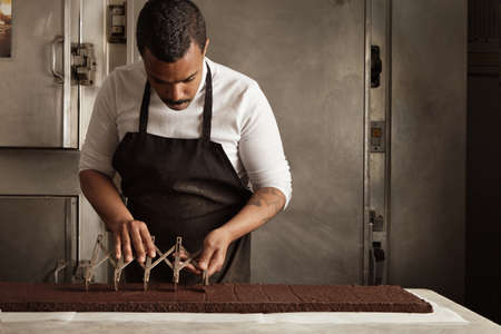 separator: Black man chief use professional vintage separator to split chocolate cake on equal portions before packaging, artisan cooking process