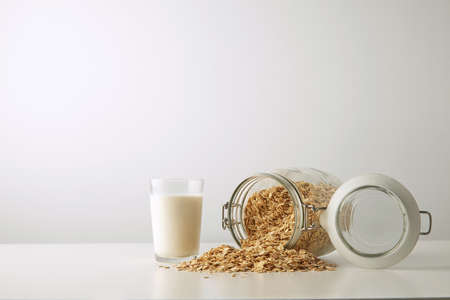 near side: Transparent glass with fresh organic milk near lying full opened rustic jar with rolled oats spread out isolated in center on white table side view LANG_EVOIMAGES