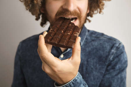 lactic: Close focus on hand,young bearded caucasian man with curly hair bites bar of tasty artisan chocolate bar LANG_EVOIMAGES