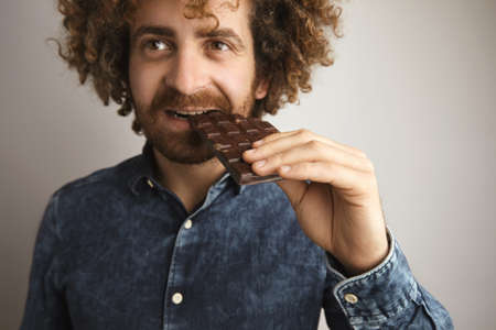 lactic: Portrait of young caucasian curly hair happy man with healthy skin bites organic freshly baked chocolate bar with side of mouth, looking in side of camera, close focus on hand