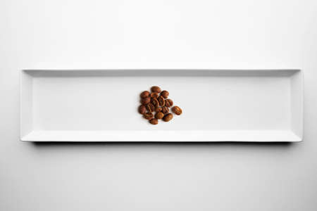 grades: Different grades of artisan professional roasting coffee isolated on white plate, top view, step four almost done baked aromatic peeled beans