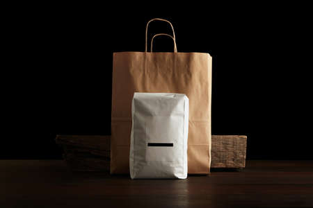 bagged: Retailer merchandise pack: big hermetic pouch white with blank label presented in front of craft paper bag and rustic wooden brick on red table, isolated on black. Coffee or tea distribution