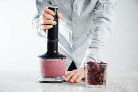 blends: Man blends frozen berries, ice, yougur and honey in blender to make healthy smoothie drink to refresh in summer time. Glass with unfocused frozen berries in front near