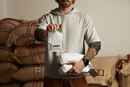 baked: Tattooed barista holds blank package bags with freshly baked coffee beans ready for sale and delivery Big bags in warehouse behind Professional alternative roasting and brewing