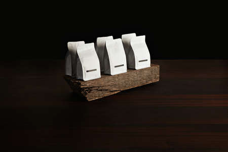 bagged: Retailer merchandise pack: six small hermetic pouches white with blank labels presented on rustic wooden brick on red table, isolated on black. Coffee or tea distribution LANG_EVOIMAGES