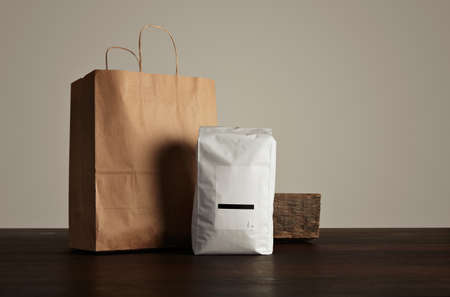 hermetic: Retailer merchandise pack: big hermetic pouch white with blank label presented near of craft paper bag and rustic wooden brick on red table, isolated on gray. Coffee or tea distribution