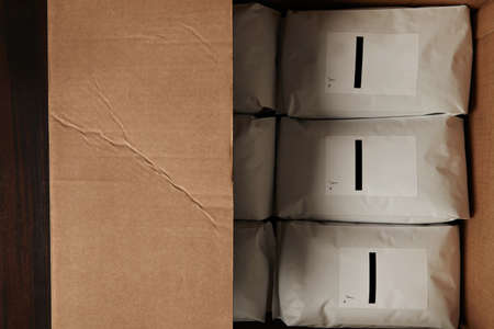 hermetic: Top view big carton box full of blank hermetic white packages with coffee or tea. Everything on red wooden table ready to sale or ship to distrubutors. Small business concept